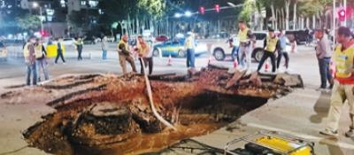 自来水管爆裂致路面塌陷事发黄河路与福州街交叉口,社区志愿者、快递小哥、过路司机设围挡疏导交通
